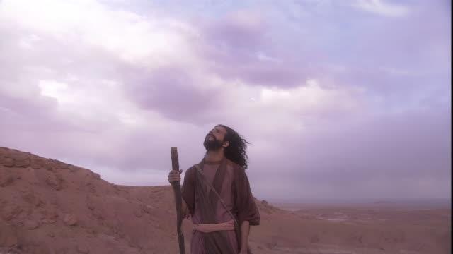 a man in biblical attire holds a staff as he looks skyward. - historische nachstellung stock-videos und b-roll-filmmaterial