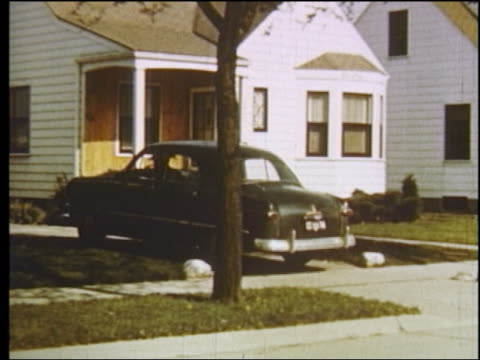 1951 pan man in black ford pulling into driveway in suburban home / son runs to greet him / detroit - 1950点の映像素材/bロール