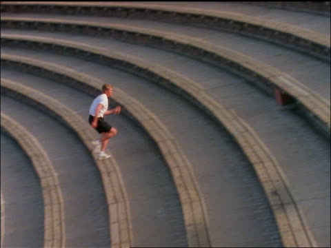 pan man in black shorts running up stadium steps / red rocks amphitheater - running shorts stock videos & royalty-free footage