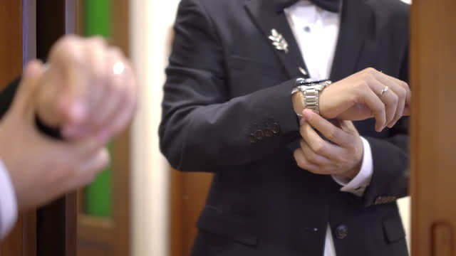 man in black suit putting his wristwatch in the wedding reception - formalwear stock videos & royalty-free footage