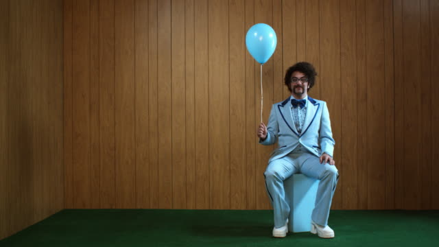 WS Man in blue suit sitting on box, holding balloon, Atlanta, Georgia, USA