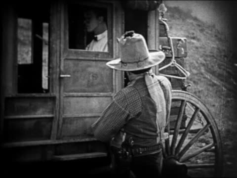 stockvideo's en b-roll-footage met b/w 1924 man in bowtie closing door of stagecoach during holdup with cowboy / feature - 1924