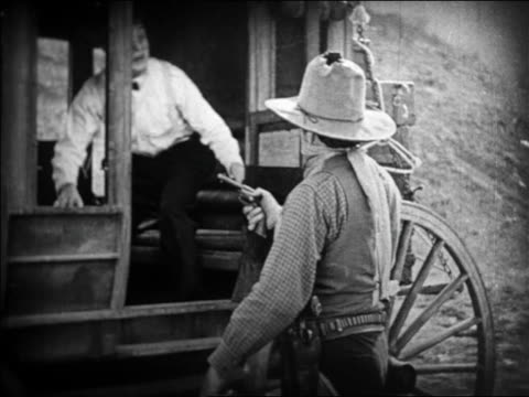 vidéos et rushes de b/w 1924 man in bowtie refusing to exit stagecoach during holdup / feature - 1924