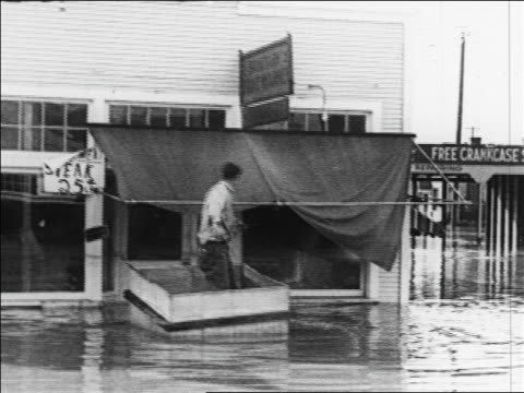 b/w 1926 man in box pushing himself with rake in flood water in town / sacramento ca / newsreel - 1926 stock videos & royalty-free footage
