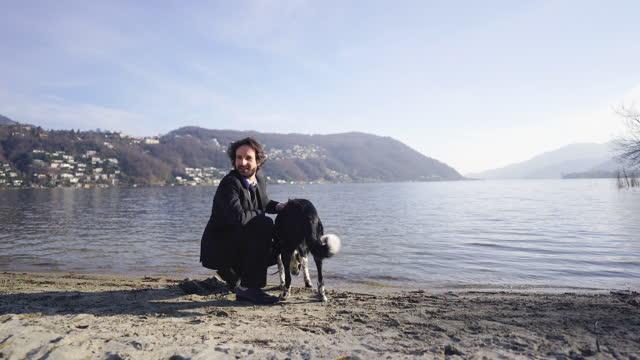 stockvideo's en b-roll-footage met mens in bedrijfskostuum het spelen met hond op meerkust, zandig strand - alleen één mid volwassen man