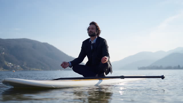 man in business suit relaxes / meditating on sup stand up paddle board on calm lake - full suit stock videos & royalty-free footage