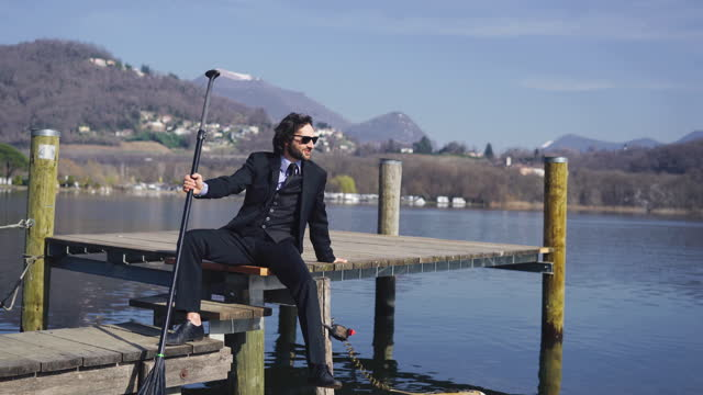 man in business suit relaxes on dock holding stand up paddle board - full suit stock videos & royalty-free footage