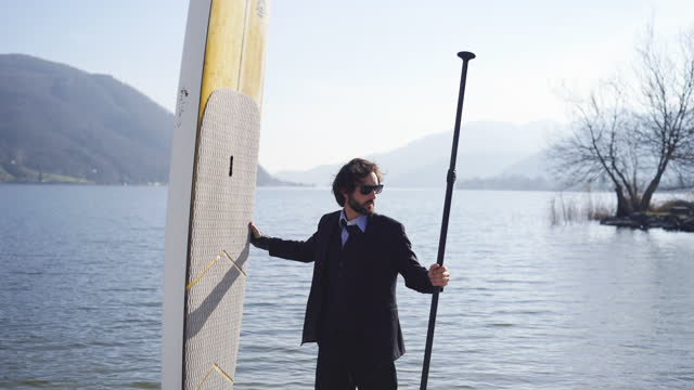 man in business suit stands on beach next to his sup stand up paddle board - next to stock videos & royalty-free footage