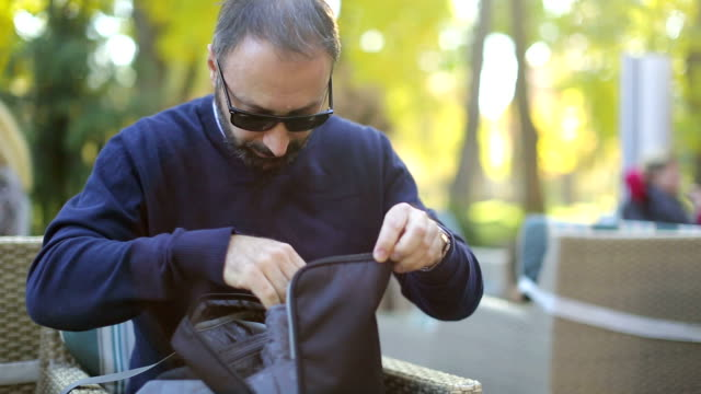 Man in cafe searching for something in his bag