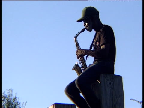 Man in cap sitting on wooden post playing saxophone partly silhouetted against blue sky at dusk