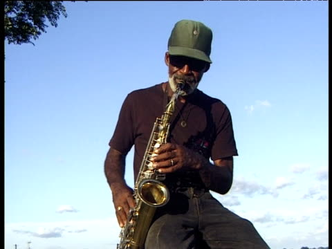 stockvideo's en b-roll-footage met man in cap wearing sunglasses sits and plays saxophone against blue sky - saxofonist