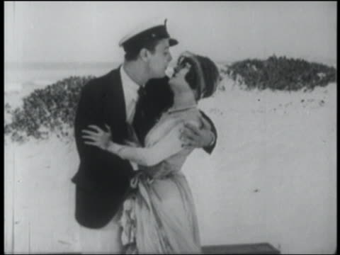 vídeos de stock, filmes e b-roll de b/w 1927 man in captain's hat talking to + passionately kissing woman on beach - esforço