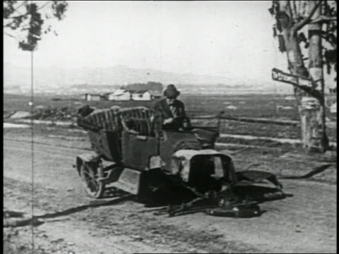 vidéos et rushes de b/w 1924 man in car (will rogers) collapsing on country road / feature - panne de voiture