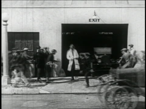 b/w 1924 man in car (will rogers) driving car quickly out of garage onto street past people / feat. - laboratorio riparazioni video stock e b–roll