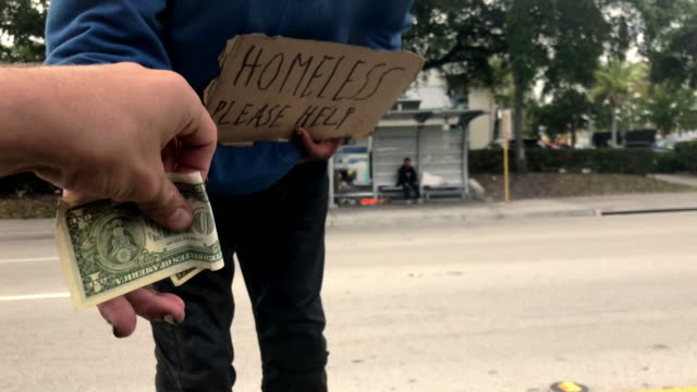 ms pov man in car giving cash to homeless person on street, miami, florida, usa - gratitude stock videos & royalty-free footage