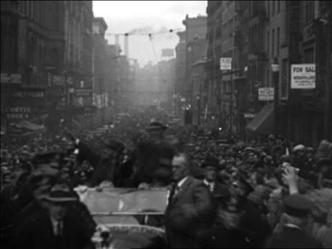 vidéos et rushes de b/w 1928 man in car waving during parade on crowded street / chicago / documentary - 1928