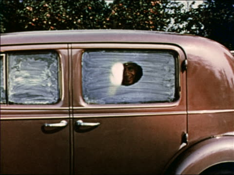 stockvideo's en b-roll-footage met 1941 man in car wipes clear circle in white on window to look out / industrial /audio - gluren
