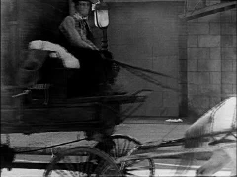 stockvideo's en b-roll-footage met b/w 1922 man (buster keaton) in cart driving away past smoke / feature - werkdier