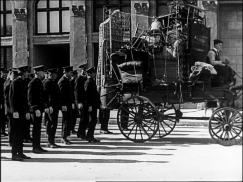 b/w 1922 man (buster keaton) in cart with police marching behind throwing bomb / it explodes / feature - buster keaton stock videos and b-roll footage