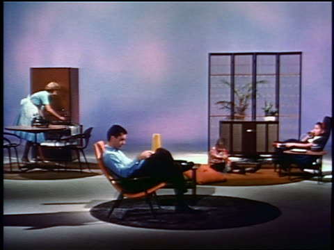 1959 man in chair reading magazine, woman taking food from freezer, children in living room (studio)