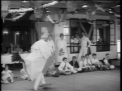 b/w 1934 man in chicken costume walking in front of children sitting on floor / adults in background - 1934 bildbanksvideor och videomaterial från bakom kulisserna