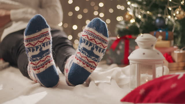 a man in christmas socks sits on a blanket near the christmas tree and types a message on his phone - sock stock videos & royalty-free footage