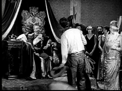 vídeos de stock, filmes e b-roll de 1924 b&w ms man in cloak meeting king/ taking off cloak to reveal cowboy gear/ king putting out hand to be kissed/ man vigorously shaking king's hand  - laço acessório