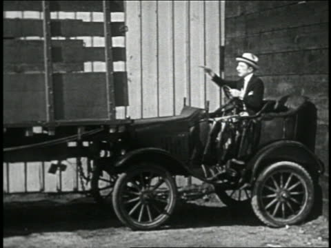 stockvideo's en b-roll-footage met b/w 1928 man (larry semon) in convertible getting smashed like an accordion by truck / feature - 1928