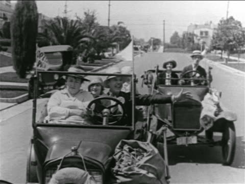 B/W 1927 man in convertible signaling to couple in car behind them / feature