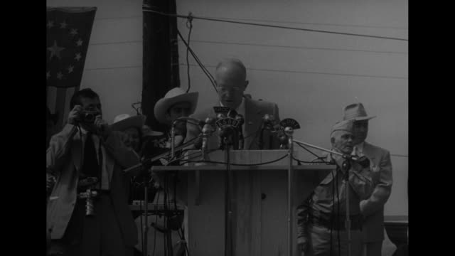 CU man in coonskin hat heavy beard and Ike buttons all over his shirt / MS man at podium introduces presidential candidate Dwight D Eisenhower...