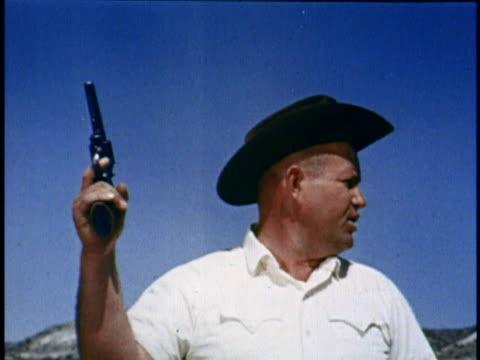 ms man in cowboy hat firing gun into the air/ usa - ヒルビリー点の映像素材/bロール
