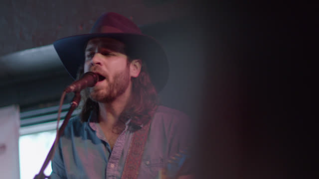 man in cowboy hat sings and plays guitar on stage in crowded austin bar - songwriter stock videos & royalty-free footage