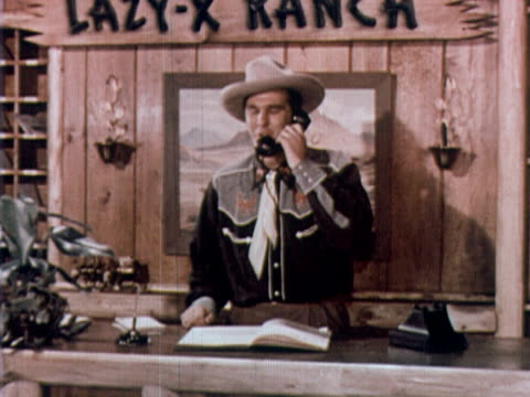 1960 ms man in cowboy hat speaking on telephone at reception desk of the 'lazy-x ranch' / usa - 電話を切る点の映像素材/bロール