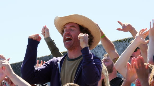 MS Man in cowboy hat standing in stadium crowd cheering with arms in air during soccer match