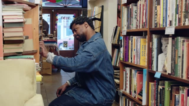 man in denim jacket browsing in bookstore - bookstore stock videos & royalty-free footage