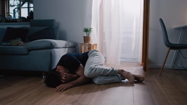 vidéos et rushes de homme de ds dans le désespoir se trouvant sur le plancher à la maison - désespoir