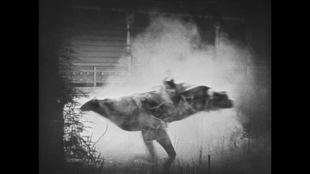 1921 man in devil costume catches fire and runs smoking from mansion - devil stock videos & royalty-free footage