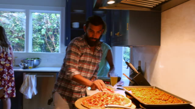 MS PAN Man in discussion with friends while making pizza in kitchen