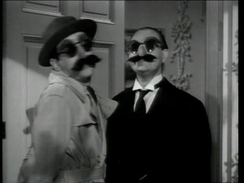 1948 MONTAGE Man in disguise demonstrating how to get into house / United States