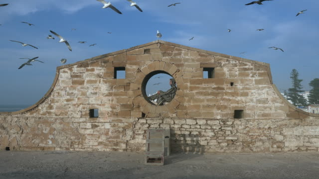 Man in djellaba sits in round window of historic stone wall