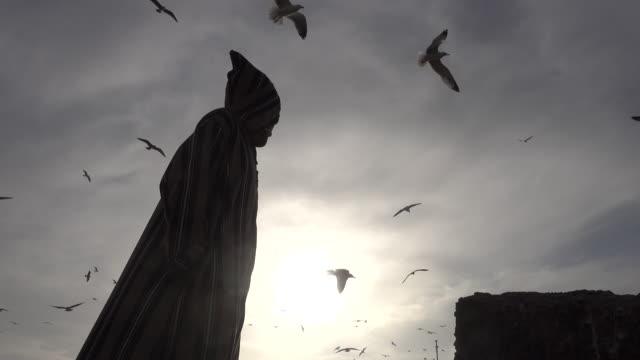 man in djellaba standing under moody sky - hood clothing stock videos & royalty-free footage