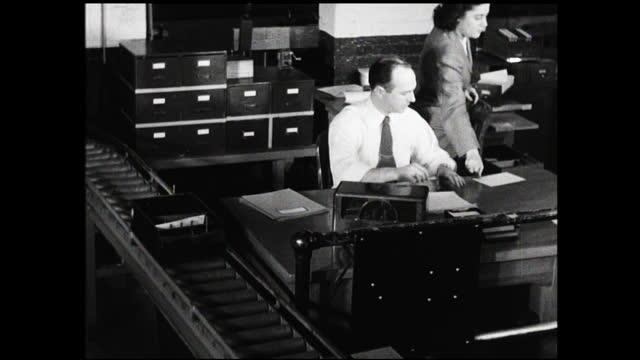 man in dress shirt and tie working behind office desk looking at paperwork next to a conveyor belt; woman sitting behind him and hands him papers - 1940 1949 bildbanksvideor och videomaterial från bakom kulisserna