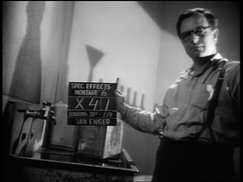 b/w 1939 man in eyeglasses holding slate between takes during movie making - film slate stock videos & royalty-free footage