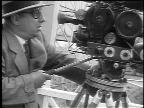 man in eyeglasses pans movie camera on tripod / palisades park, nj / newsreel - palisades park stock videos & royalty-free footage