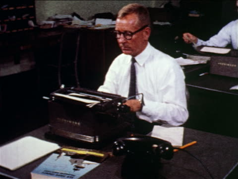1960 man in eyeglasses typing on typewriter at desk in newspaper office / documentary - journalism stock videos & royalty-free footage