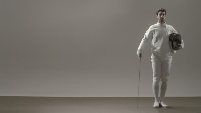 ws man in fencing uniform posing against white background while holding mask and foil/ man bowing/ new york, newyork - stoppelbart stock-videos und b-roll-filmmaterial