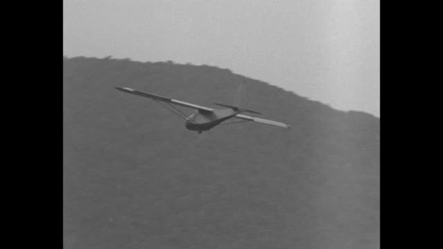 Man in field holding arm up glider takes off can see pilot's head and rope attached to nose fall away / glider soaring it makes turn / glider from...