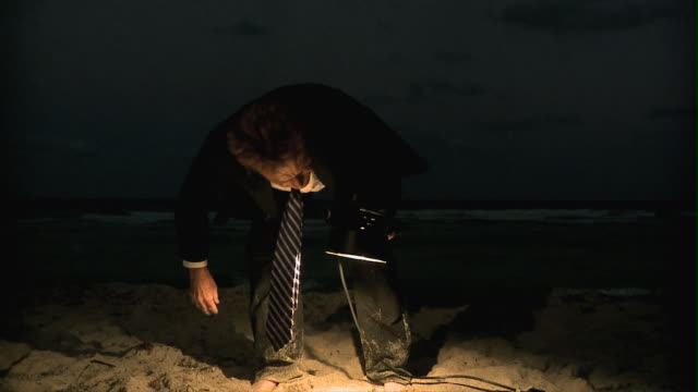 slo mo ms man in full suit holding spot light, searching in sand at night, south beach, florida, usa - full suit stock videos & royalty-free footage