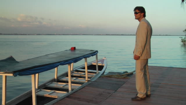 slo mo, ws, man in full suit standing on deck in early evening, turning and smiling to camera, portrait, manaus, brazil - full suit stock videos and b-roll footage