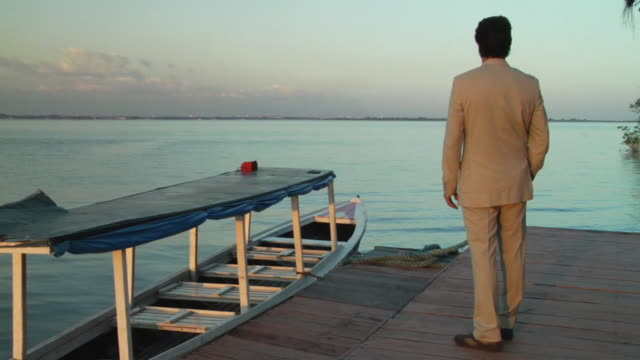 slo mo, ws, man in full suit standing on deck in early evening, turning and smiling to camera, portrait, manaus, brazil - full suit stock videos & royalty-free footage